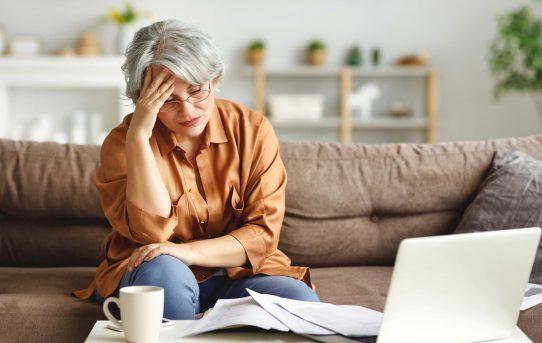 Kvinna framför dator orolig över sin ekonomi